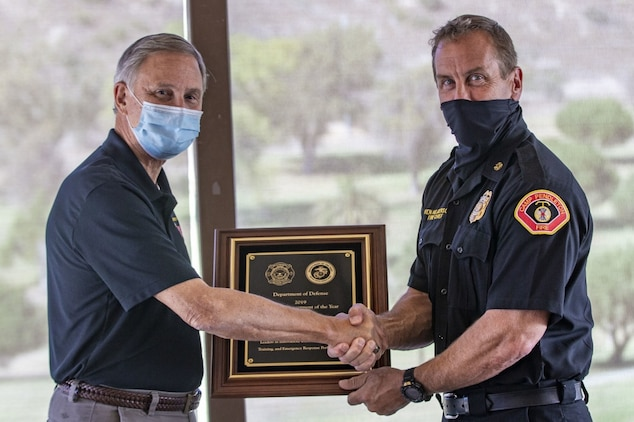 Acting Under Secretary of the Navy Gregory J. Slavonic hands a plaque for the Department of Defense's Large Fire Department of the Year award to Ken Helgerson, the fire chief for the Camp Pendleton Fire Department, during a ceremony at Marine Memorial Golf Course on Marine Corps Base Camp Pendleton, California, Oct. 27, 2020. This is the sixth time CPFD has been selected for the award. Slavonic traveled to Southern California to meet with sailors and Marines, gaining enhanced insight to fleet modernization, cyber and readiness efforts that will ultimately build a more lethal force. (U.S. Marine Corps photo by Lance Cpl. Drake Nickels)