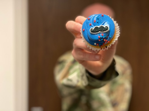 An Airmen holds a cupcake with a moustache decoration up to the camera.
