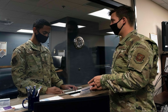 Airman hands paperwork to other Airman
