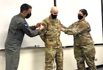 Staff Sgt. Garrett McNeely, 12th Operations Support Squadron Aerospace Physiology non-commissioned officer in charge of logistics, receives his technical sergeant stripes from  Lt. Col. Jeffrey Cameron, 12th OSS commander, and Maj. Heather Tevebaugh, 12 AOP flight commander, under the Air Force's Stripes for Exceptional Performers Nov. 13 at Joint Base San Antonio-Randolph.