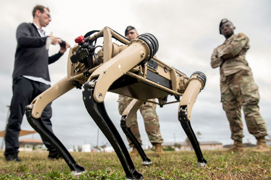 Two airmen stand in a field and look at a four-legged robot as a civilian speaks to them.