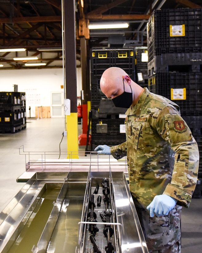 U.S. Air Force Tech. Sgt. Kyle Deconnick, 52nd Logistics Readiness Squadron NCOIC of Individual Protective Equipment, cleans an M4 using a new ultrasonic weapons cleaner at Spangdahlem Air Base, Germany, Nov. 9, 2020. Deconnick led the way to acquiring the machine to enhance the weapons cleaning process and save man hours. (Air Force photo by Senior Airman Chanceler Nardone)