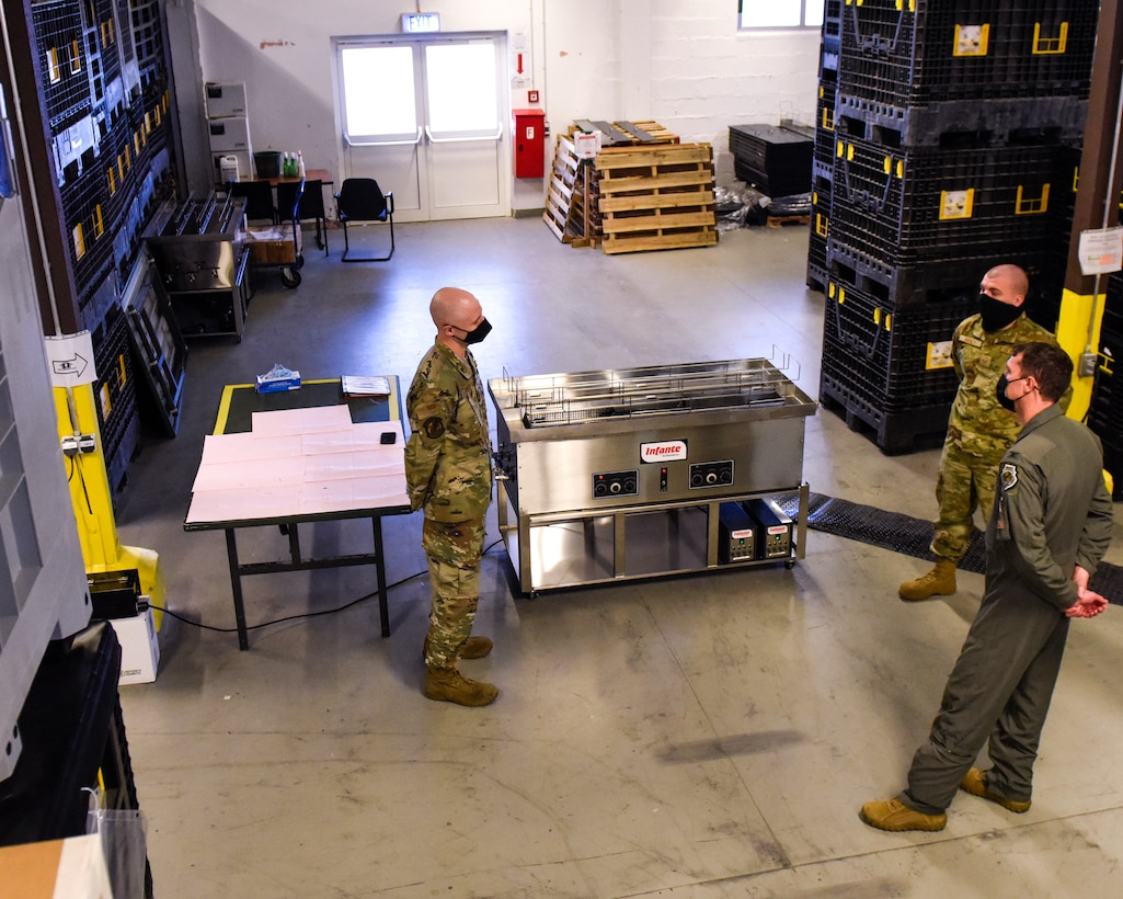 Two members of the 52nd Logistics Readiness Squadron greet U.S. Air Force Col. David C. Epperson, 52nd Fighter Wing commander, bottom right, before showing him a new ultrasonic weapons cleaner at Spangdahlem Air Base, Germany, Nov. 9, 2020. The machine allows for a two-member team to get 60 M4s inspection-ready on one typical workday shift. (U.S. Air Force photo by Senior Airman Chanceler Nardone)