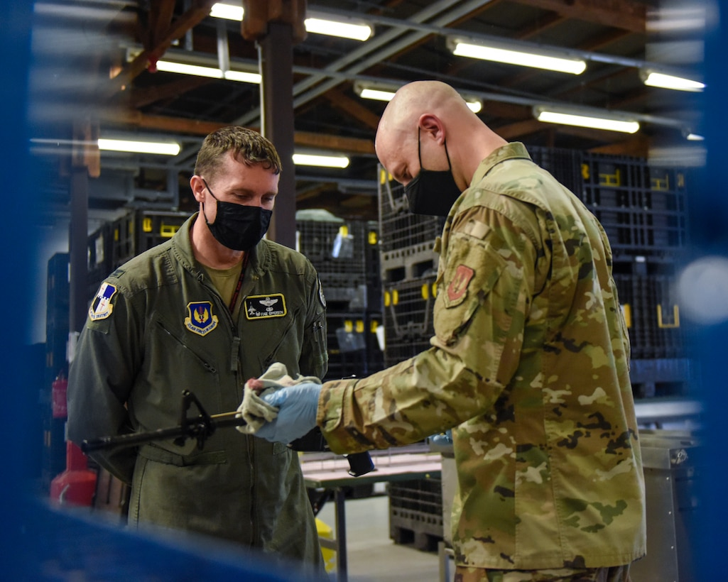 U.S. Air Force Tech. Sgt. Kyle Deconnick, 52nd Logistics Readiness Squadron NCOIC of individual protective equipment, right, shows U.S. Air Force Col. David C. Epperson, 52nd Fighter Wing commander, left, an M4 once it has been cleaned using a new ultrasonic weapons cleaner at Spangdahlem Air Base, Germany, Nov. 9, 2020. The demonstration lasted around 30 minutes and allowed wing leadership to see tangible results of the new process.  (U.S. Air Force photo by Senior Airman Chanceler Nardone)