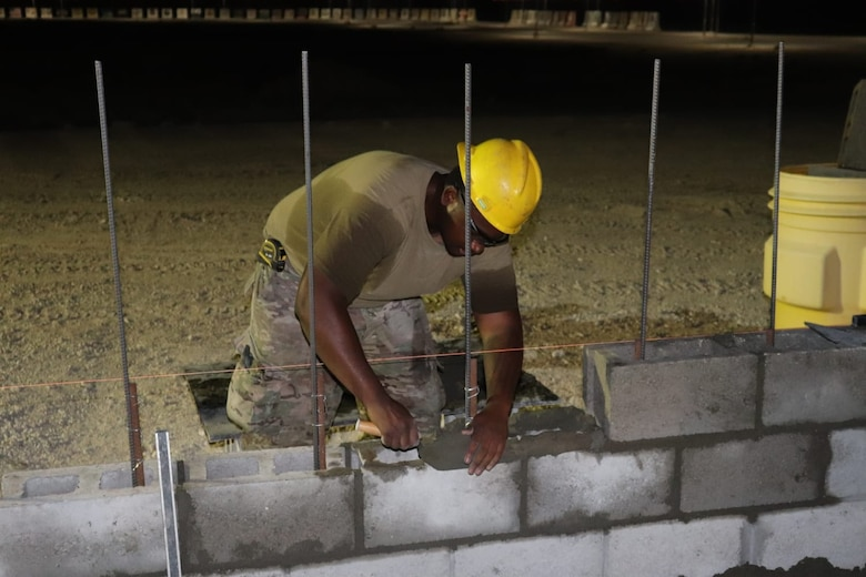 A member of the 310th Engineering Detachment works on construction a Joint Air Ground Station building in Qatar. The building is being built using troop labor from a design from the U.S. Army Corps of Engineers Middle East District's Center of Standardization for Nonpermanent Facilities (COS). The COS maintains a library of off the shelf designs that can be adapted for almost any purpose. Using COS designs can save significant time and money in the construction process.