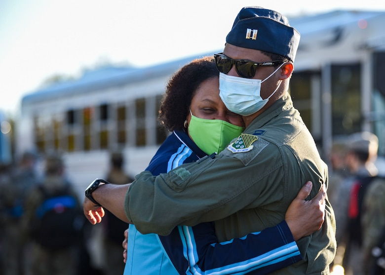 An Airman gives his mother a hug goodbye before boarding a bus to leave for deployment.