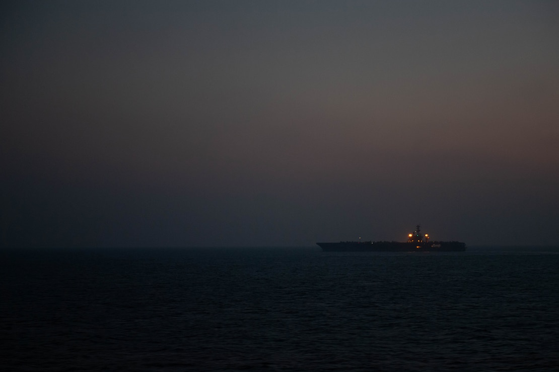 USS Nimitz (CVN 68) underway as night falls in the Arabian Sea.