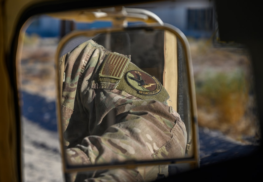 Arm of an Airman reflected in a side-view mirror of a Humvee.