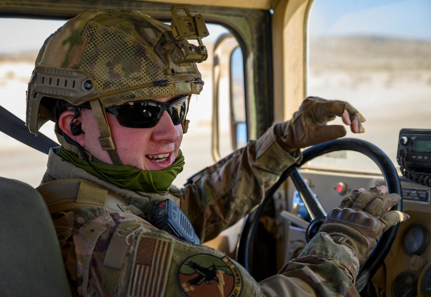 Airman smiles while seated behind the steering wheel of a Humvee.