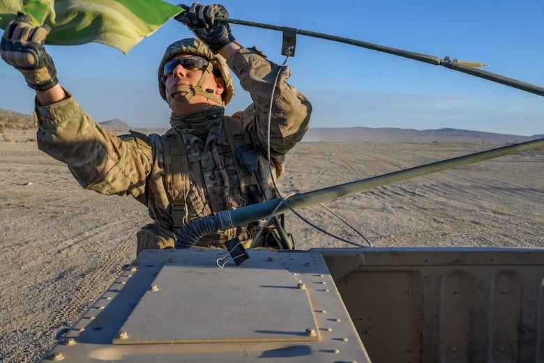 Airman grabs a flag on the back of a Humvee.
