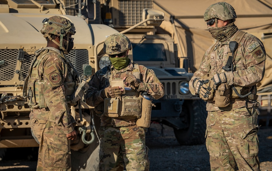 Three Airmen stand in front of vehicles and talk.