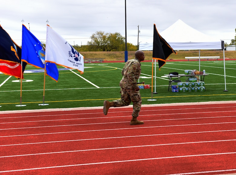 U.S. Air Force Col. James Finlayson, 17th Training Wing vice commander, begins the Prisoner of War and Missing in Action 24 hour remembrance run by making the first lap around the track with the baton. During the run the baton never stopped moving. (U.S. Air Force photo by Airman 1st Class Dominique Parham)