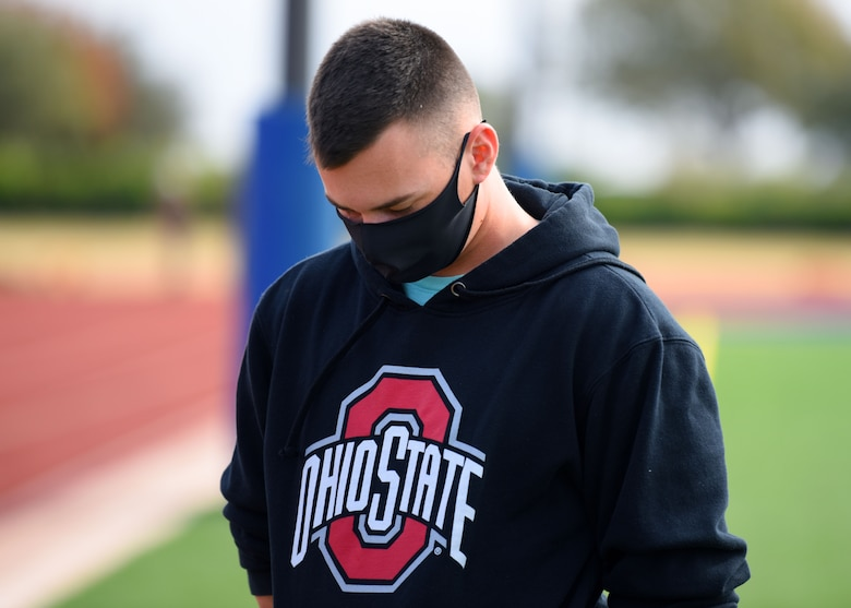 A 312th Training Squadron student bows his head during a moment of silence at the Prisoner of War and Missing in Action 24 hour remembrance run on the Mathis Fitness Center track on Goodfellow Air Force Base, Texas, Nov. 14, 2020. Over 1,500 American heroes are still missing and unaccounted for from the Vietnam War. (U.S. Air Force photo by Airman 1st Class Ethan Sherwood)