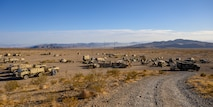 Military vehicle and tents at the bottom of a road in the desert.