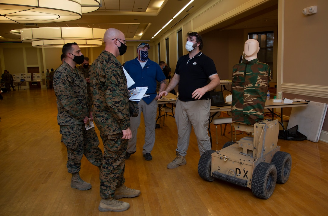 Mathew Cork, right, manager for Marathon Targets, informs Marines with 2nd Marine Division about the use of robotic targets during combat simulations for effective fire and movement during the Warfighter Training Symposium at Marston Pavilion on MCB Camp Lejeune, North Carolina, Nov. 4, 2020. The symposium provided more than 150 leaders with information on facilities available on MCB Camp Lejeune to Marines for training and provides an opportunity to inquire about range complex capabilities. (U.S. Marine Corps photo by Cpl. Ginnie Lee)