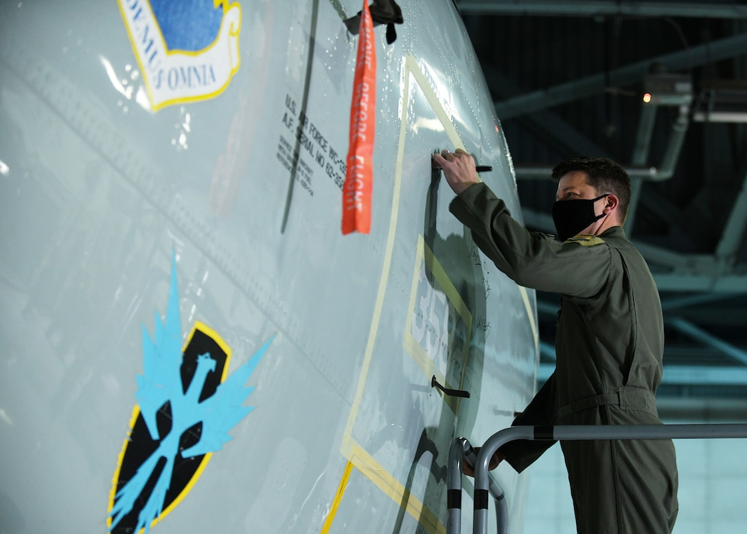 Man in flight suit signs aircraft as it is retired.