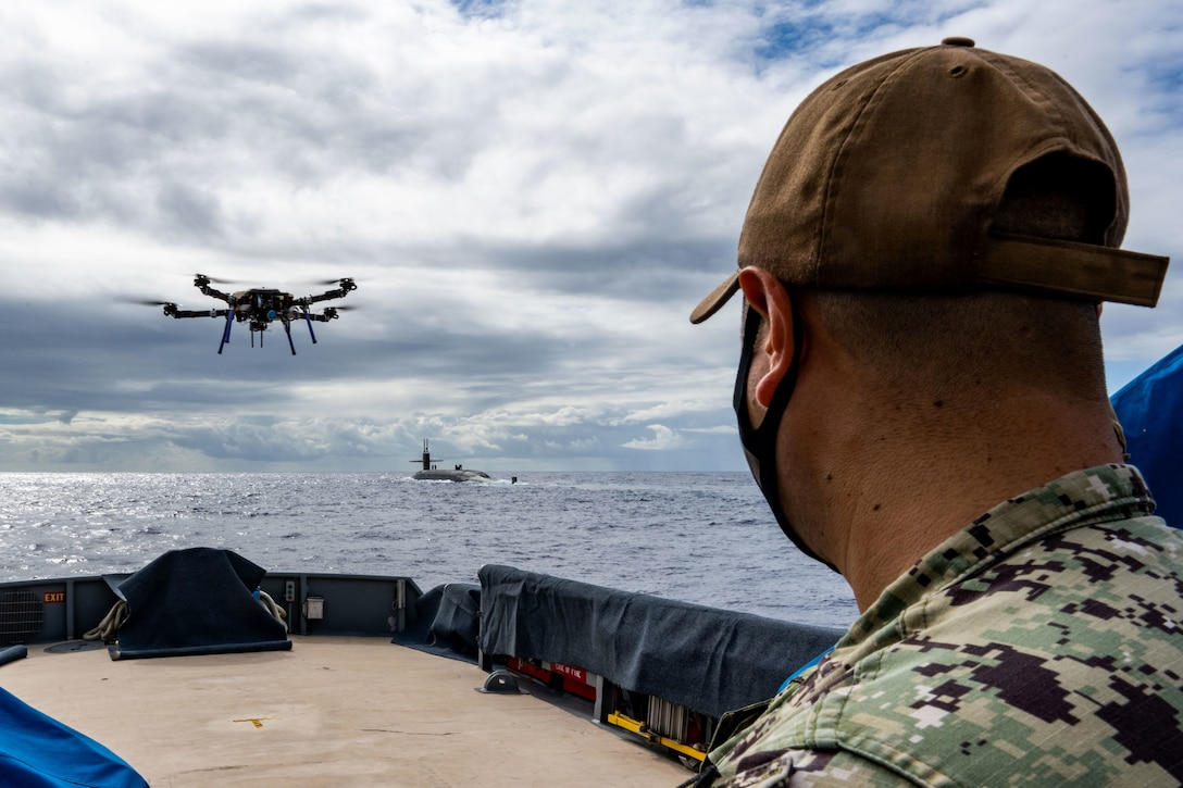 A sailor watches a drone fly over the water, with a submarine in the distance.