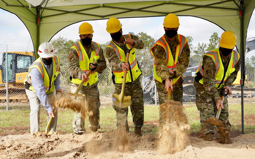 Photo of five people shoveling dirl