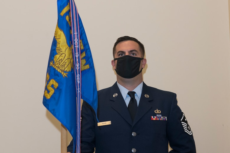 An Airman stand at attention while holding the unit's guidon