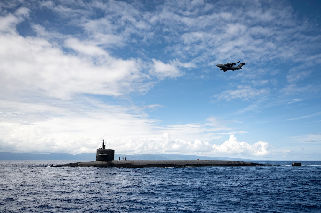 An aircraft flies over a submarine in the water.