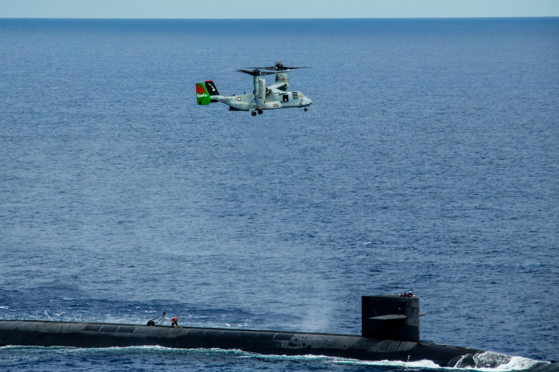 A Marine Corps Osprey aircraft flies above a Navy submarine in blue waters.