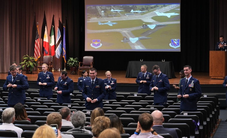 The graduating class of 21-02 stands to break their silver wings in half Nov. 13, 2020, on Columbus Air Force Base Miss. To graduate, students completed 52 weeks of pilot training with six-weeks of preflight academics and physiological training followed by primary training. (U.S. Air Force photo by Senior Airman Jake Jacobsen)
