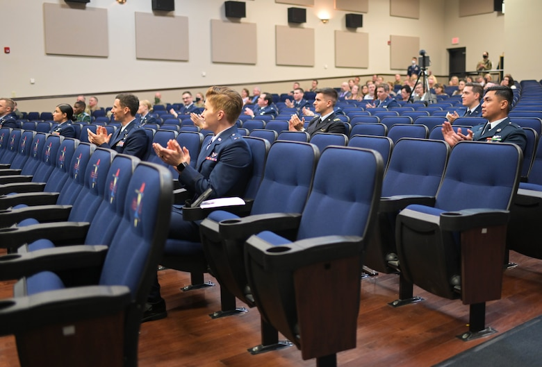 U.S. Air Force and international student pilots from class 21-02 clap for one of their fellow classmates receiving a diploma Nov. 13, 2020, on Columbus Air Force Base Miss. As a result of COVID-19 restrictions the graduation was live streamed to Facebook on the Columbus AFB page for viewers not in attendance. (U.S. Air Force photo by Senior Airman Jake Jacobsen)