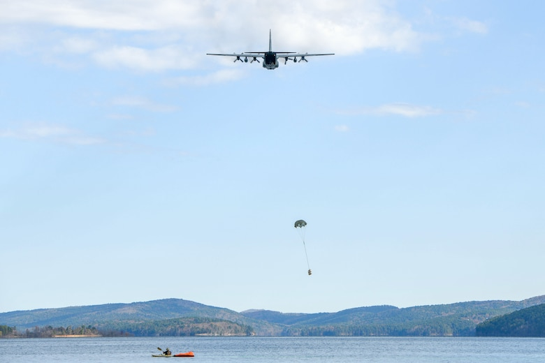Plane flying over lake dropping small package