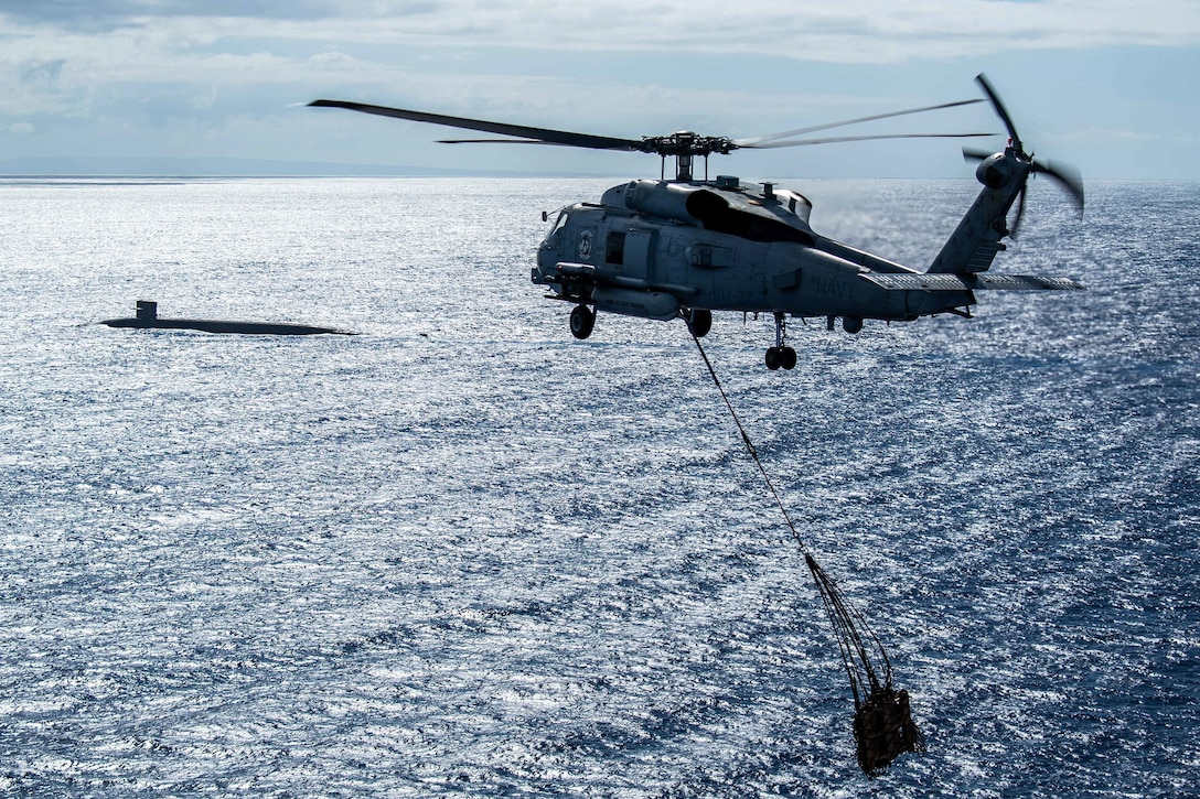 A helicopter with cargo suspended beneath it approaches a submarine in water.