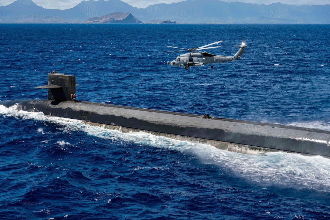 A Navy helicopter flies above a submarine in blue water.