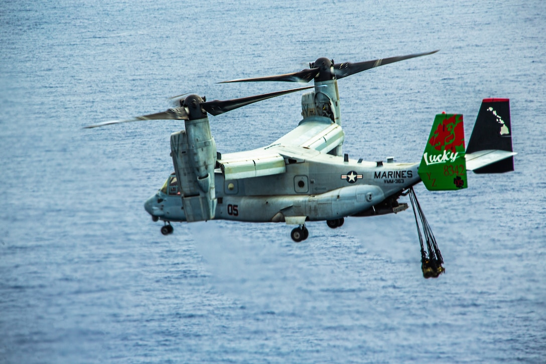 A Marine Corps Osprey aircraft flies with a cargo suspended beneath it.