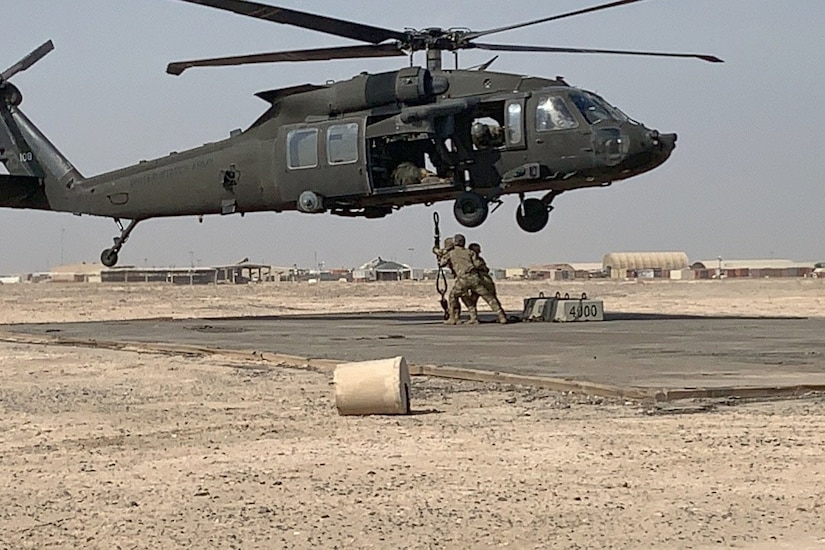 Soldiers sling load a helicopter.