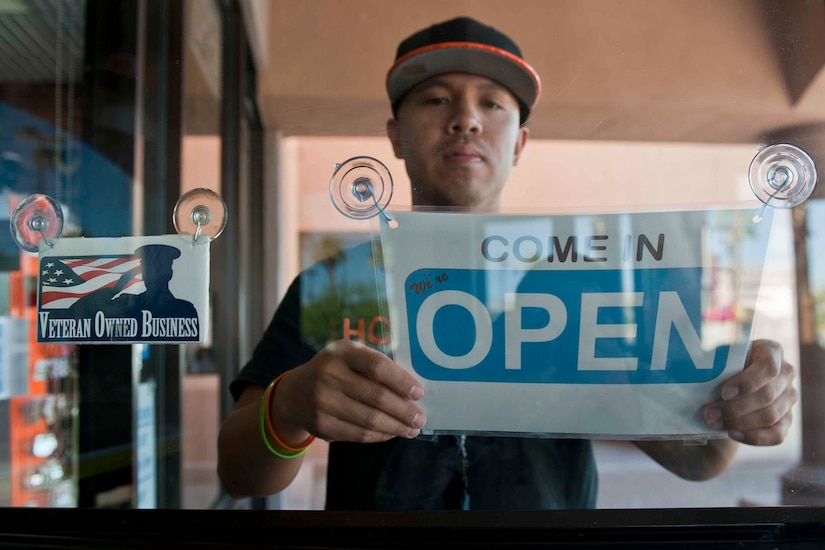 "A man places an ""open"" sign on a glass door."