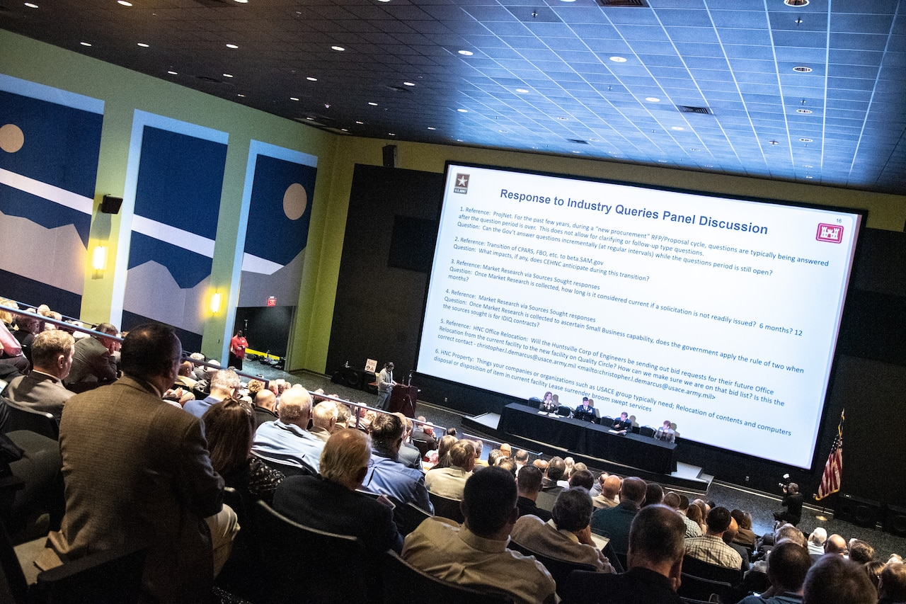 Hundreds of individuals sit in an auditorium and look at a slide presentation.