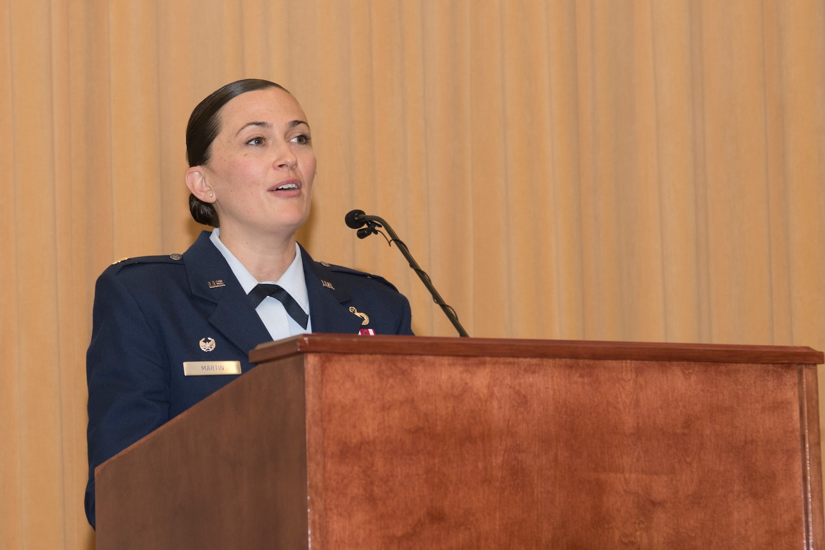 An Airman speaks while standing at a podium