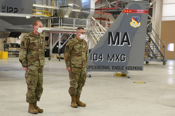 Master Sgt. Leo Burbee, 104th Maintenance Group structural maintenance supervisor, and Master Sgt. Bob Oleksak, 104MXG fabrication element supervisor, stand at attention after receiving the Air Force Achievement Medal during a ceremony Nov. 14, 2020, at Barnes Air National Guard Base, Massachusetts.