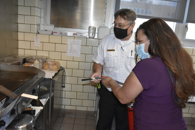 Arnold Air Force Base Fire and Emergency Services Fire Prevention Inspector Steve Macon, left, demonstrates to Paula Lyle the proper way to use a fire extinguisher Nov. 9, 2020, at Arnold Air Force Base, Tenn. Ensuring a fire extinguisher is kept nearby when cooking is one of several fire prevention tips Arnold FES has provided ahead of the Thanksgiving holiday. (U.S. Air Force photo by Bradley Hicks)