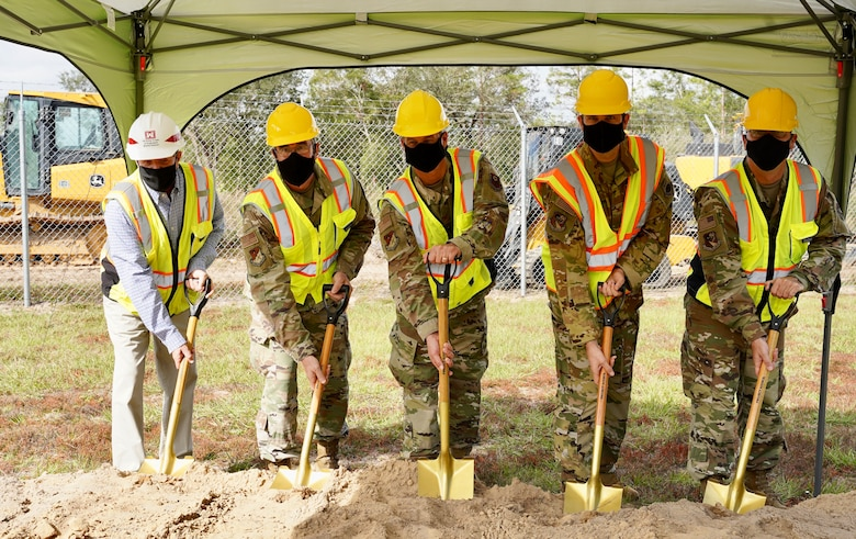 Photo of five people standing with shovels next to a dirt mound