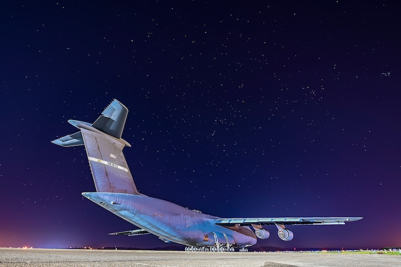 A very large grey airplane sits on the flight line under the stars.