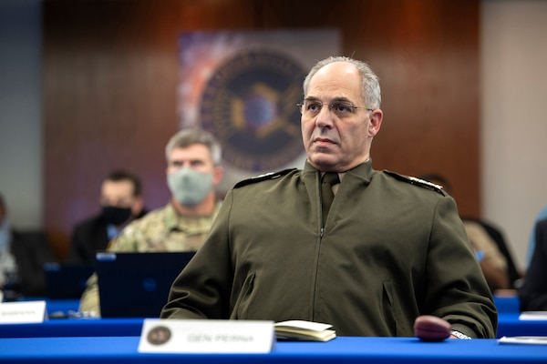 A military officer watches a simulated exercise.