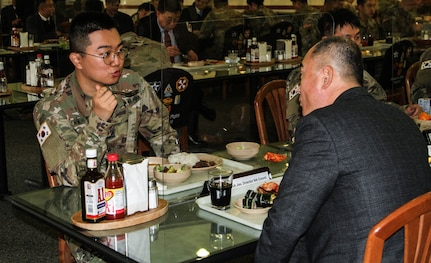 A KATUSA soldier talks with a member of South Korea's National Assembly Defense Committee during lunch.