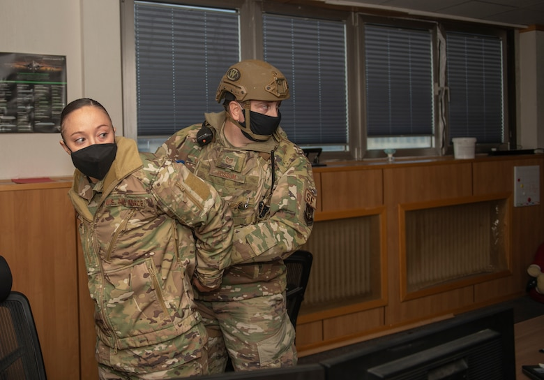 U.S. Air Force Tech. Sgt. Brian Fossum, 52nd Security Forces flight sergeant, right, apprehends Staff Sgt. Shealyn Kunze, 52nd SFS resource protection NCOIC, who posed as an active shooter during a base-wide exercise at Spangdahlem Air Base, Germany, Nov. 16, 2020. The active shooter exercise tested the response time of multiple base agencies and their ability to control the situation. (U.S. Air Force photo by Senior Airman Ali Stewart)