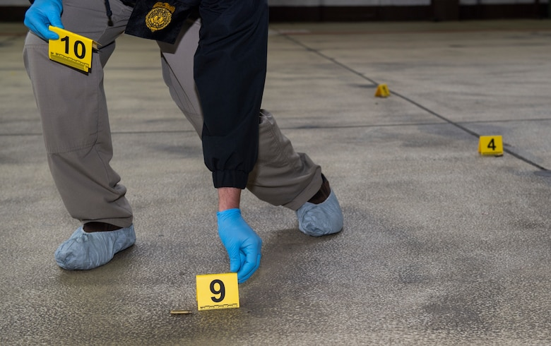 U.S. Air Force Office of Special Investigations special agent places evidence markers at the scene of an active shooter exercise at Spangdahlem Air Base, Germany, Nov. 16, 2020. The active shooter exercise simulated an entire scenario in which OSI responded to the scene, collected evidence, and later interrogated the suspect. (U.S. Air Force photo by Senior Airman Ali Stewart)