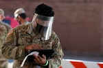 Pfc. Pedro Dominguez, assigned to the North Carolina Army National Guard's 875th Engineer Company, enters a patient's information at a drive-thru COVID-19 test site in High Point, North Carolina, on Nov. 13, 2020. More than 170 North Carolina National Guard Soldiers and Airmen are activated across the state to support N.C. Emergency Management's response to the pandemic.