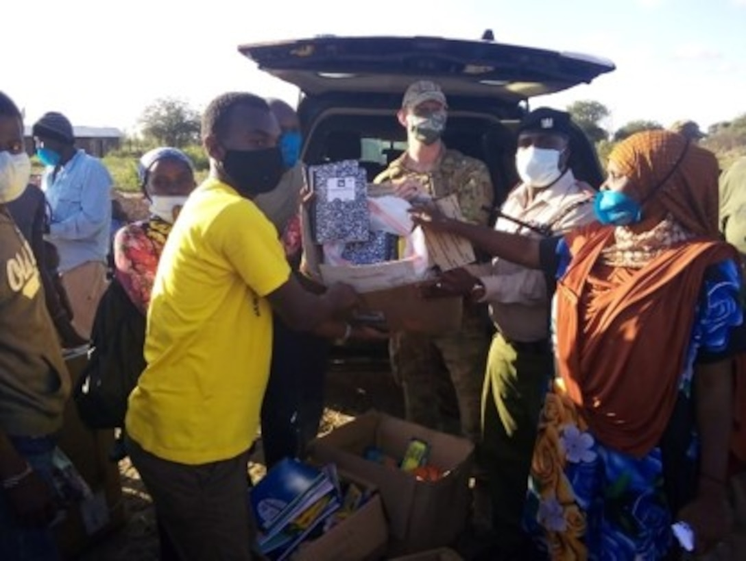U.S. Air Force Capt. Ian Latham, 475th Expeditionary Air Base Squadron deputy force commander, presents school supplies for the teachers to gift to students when school opens back up in Magogoni Village at Manda Bay, Kenya, Nov. 6, 2020.