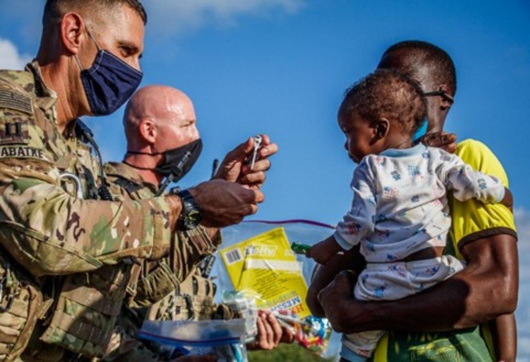 U.S. Army Capt. Jeffrey Sabatke, company commander of alpha company Task Force Bayonet, passes out supplies and candy to children In Magogoni Village at Manda Bay, Kenya, Nov. 6, 2020.