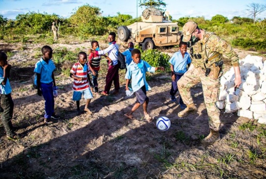 .S. Air Force Capt. Ian Latham, 475th Expeditionary Air Base Squadron deputy force commander, plays soccer with kids from the village of Magogoni at Manda Bay, Kenya, Nov. 6, 2020.