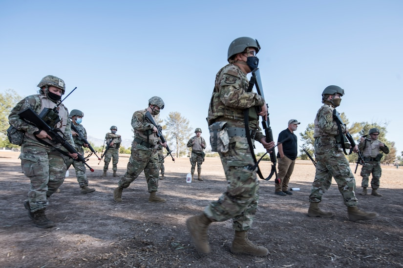 Airmen move through a field while holding weapons.