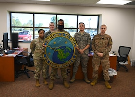 U.S. Air Force Airmen of the 14th Communications Squadron Client Systems Technician shop, pose with their squadron logo Nov. 2, 2020, on Columbus Air Force Base, Miss. The CST shop has successfully updated over a 1,000 devices with outdated Basic Input Output Systems base wide. (U.S Air Force photo by Senior Airman Jake Jacobsen)