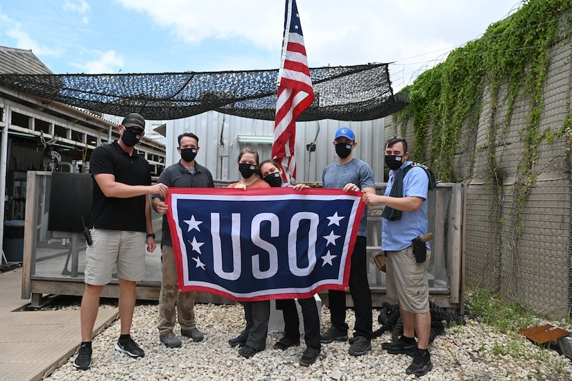 Men and women pose with a USO flag while in front of a U.S. flag.
